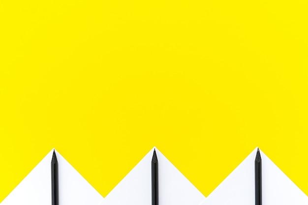 Adesivi bianchi con matite nere allineati con un motivo geometrico su giallo