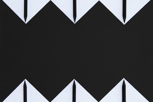 Adesivi bianchi con matite nere allineati con un motivo geometrico su nero