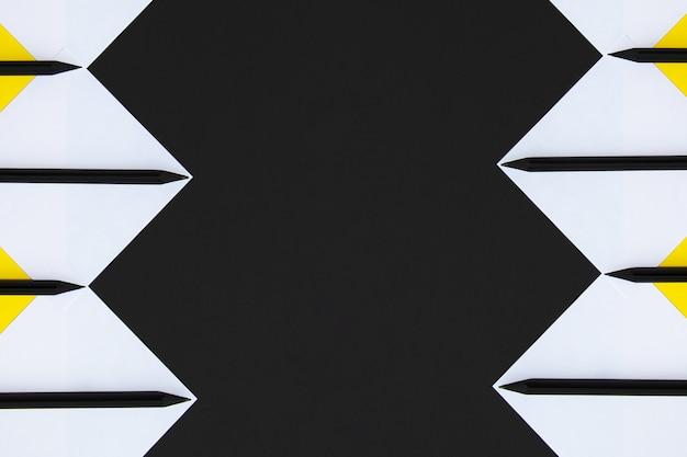 Adesivi bianchi e gialli con matite nere allineati con un motivo geometrico su uno sfondo nero.