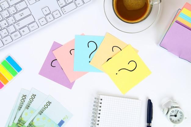 Adesivi nota con il punto interrogativo sul desktop bianco accanto a una tazza di caffè e tastiera