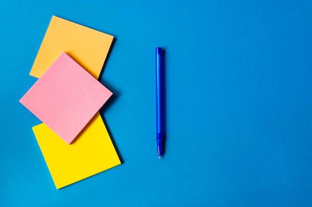 Adesivi per appunti e penna si trovano su uno sfondo blu.
