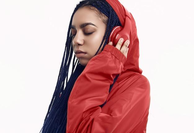 Adolescente africano con i dreadlocks nella musica d'ascolto della giacca a vento rossa