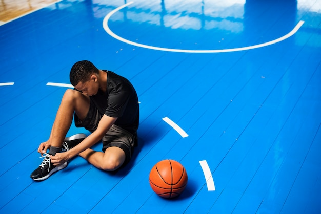 Adolescente afroamericano che lega i suoi laccetti su un campo da pallacanestro