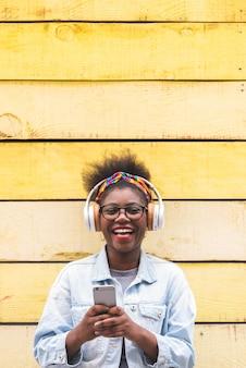 Adolescente afroamericano che per mezzo del telefono cellulare all'aperto