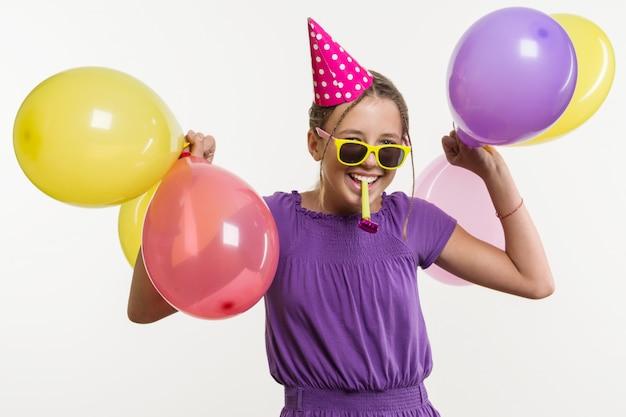 Adolescente allegro con palloncini, in cappello festivo, soffiando un tubo