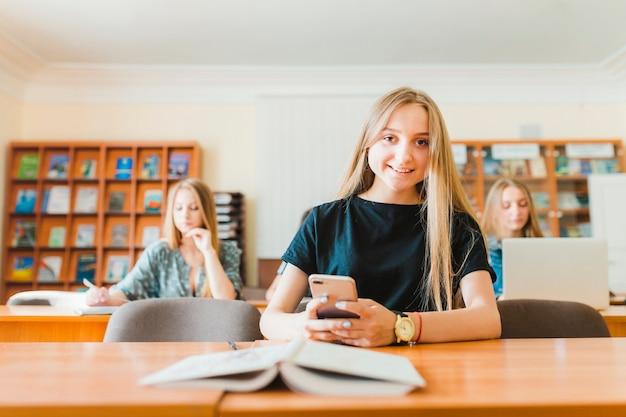 Adolescente allegro con smartphone vicino al libro di testo