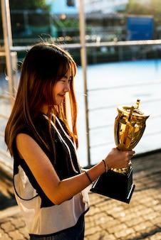 Adolescente asiatica in vestiti sportivi che tengono un trofeo all'aperto