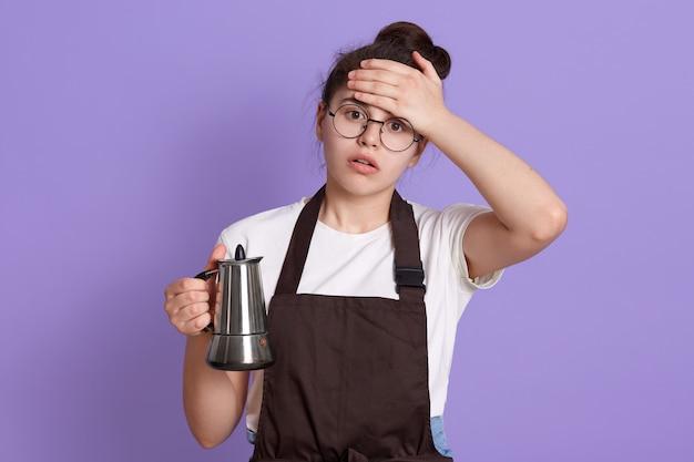 Adolescente attraente stanco che indossa maglietta bianca e grembiule marrone, tenendo in mano tè o caffettiera