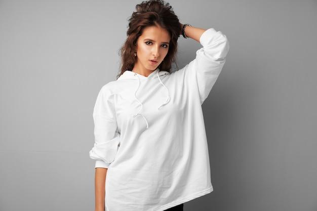 Adolescente bello della donna nella posa bianca di maglia con cappuccio