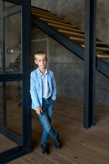 Adolescente bionda, in una camicia e jeans alla moda, si trova in un appartamento in stile loft e sorride ampiamente