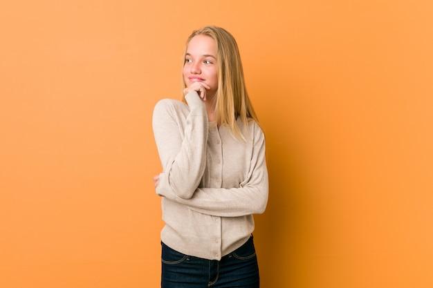 Adolescente caucasico sveglio che posa condizione contro una parete arancione