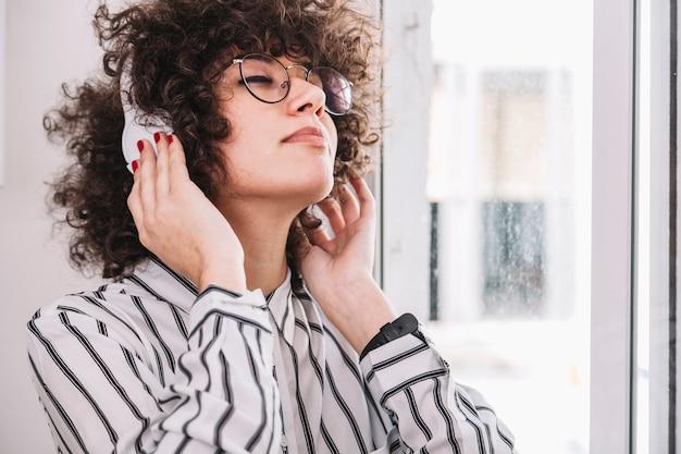 Adolescente che ascolta la musica vicino alla finestra