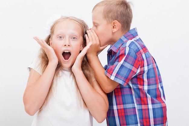 Adolescente che bisbiglia nell'orecchio un segreto alla ragazza teenager