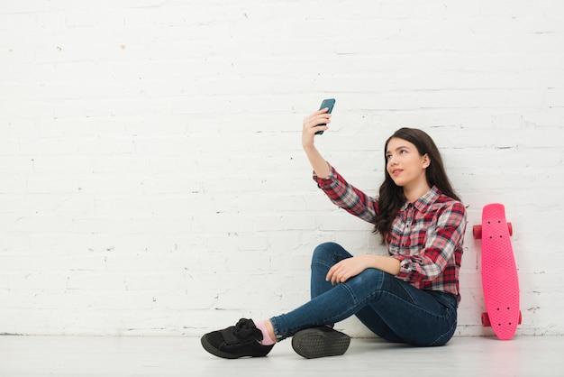 Adolescente che cattura un selfie
