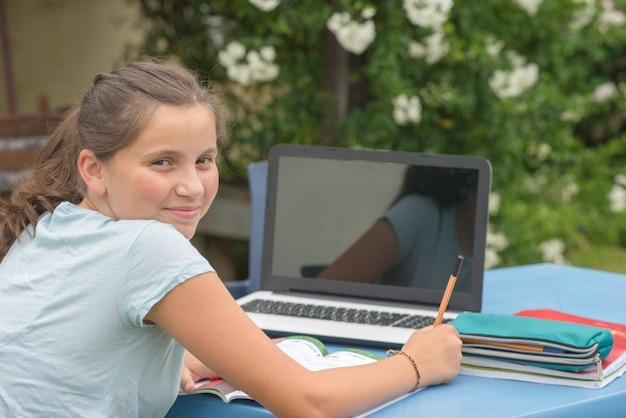 Adolescente che fa i suoi compiti con il computer portatile nel giardino