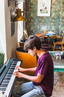 Adolescente che gioca piano nel caffè accogliente