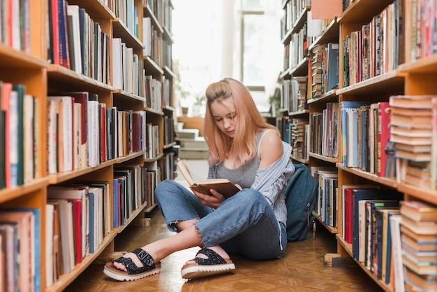 Adolescente che legge vicino allo zaino