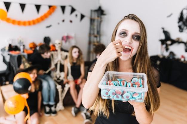 Adolescente che mangia marmellata d'arance sulla festa di alloween