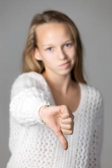 Adolescente che mostra il pollice verso il basso