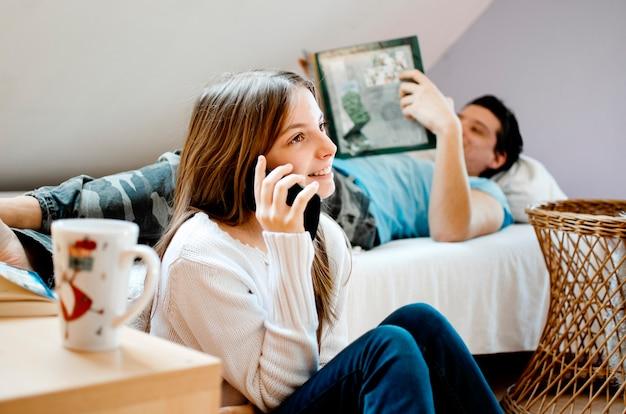 Adolescente che per mezzo del telefono cellulare mentre il suo amico che mette su letto che legge un libro. rilassanti giovani amici a casa. l'adolescenza tra fratelli e sorelle si gode il tempo della famiglia in camera