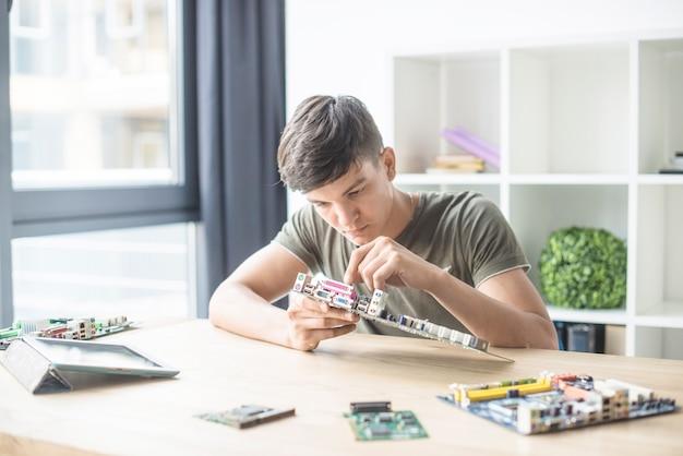 Adolescente che ripara la scheda madre del computer sullo scrittorio di legno