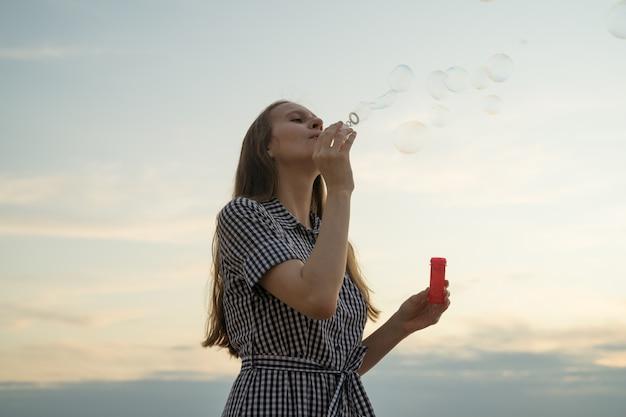 Adolescente che soffia bolle di minestra