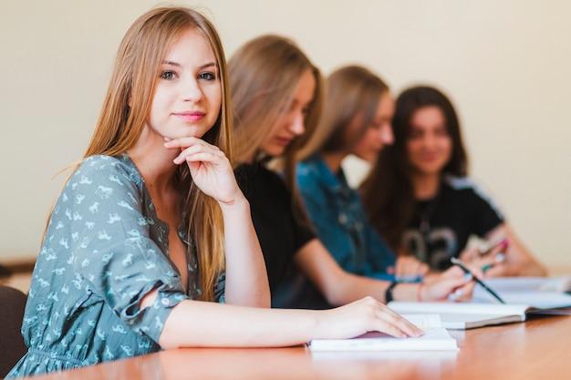 Adolescente che studia vicino agli amici