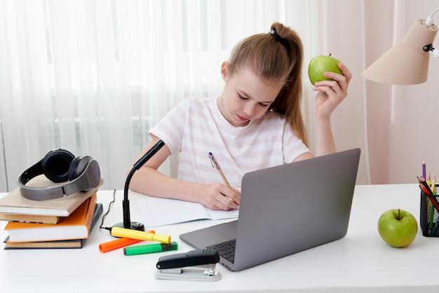 Adolescente che tiene mela verde che studia a casa con il computer portatile