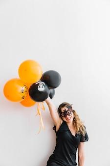 Adolescente con halloween torvo che tiene gli aerostati arancioni e neri