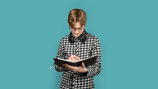 Adolescente con i capelli rossi in una camicia stridula su un colore