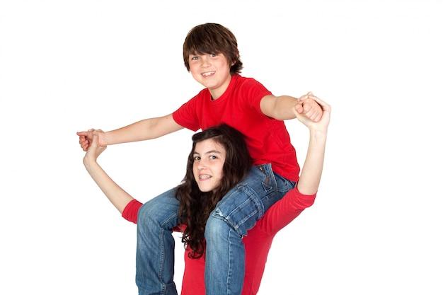 Adolescente con il ragazzino sulle sue spalle isolato su fondo bianco