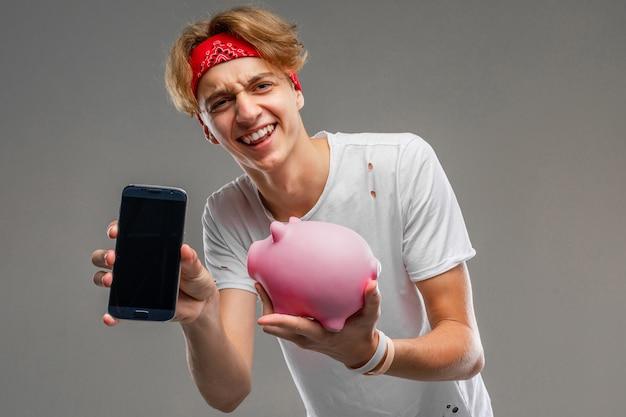 Adolescente con salvadanaio in posa contro grigio, giovane uomo in una maglietta leggera su uno sfondo grigio muro