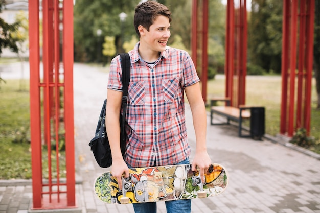 Adolescente con skateboard vicino a pilastri di metallo