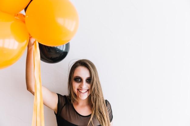 Adolescente con spaventoso torvo e palloncini neri e arancioni