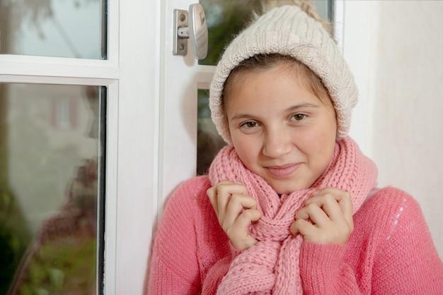 Adolescente con un maglione e un cappello rosa