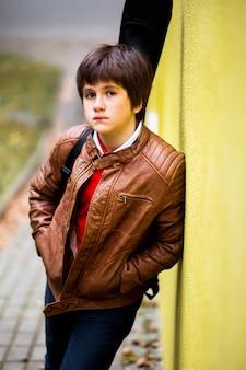 Adolescente del ragazzo che propone contro una priorità bassa gialla della parete