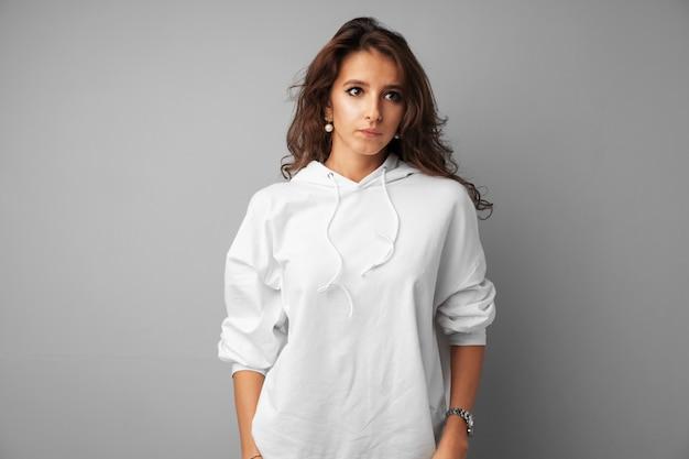 Adolescente della bella donna in maglia con cappuccio bianca che posa sopra un gray