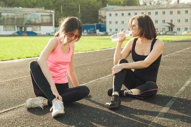 Adolescente della figlia e della madre che riposa dopo l'allenamento