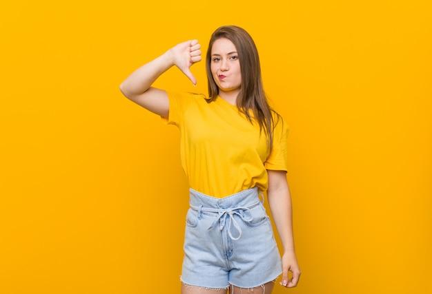 Adolescente della giovane donna che indossa una camicia gialla che mostra un gesto di avversione, pollici giù. concetto di disaccordo.