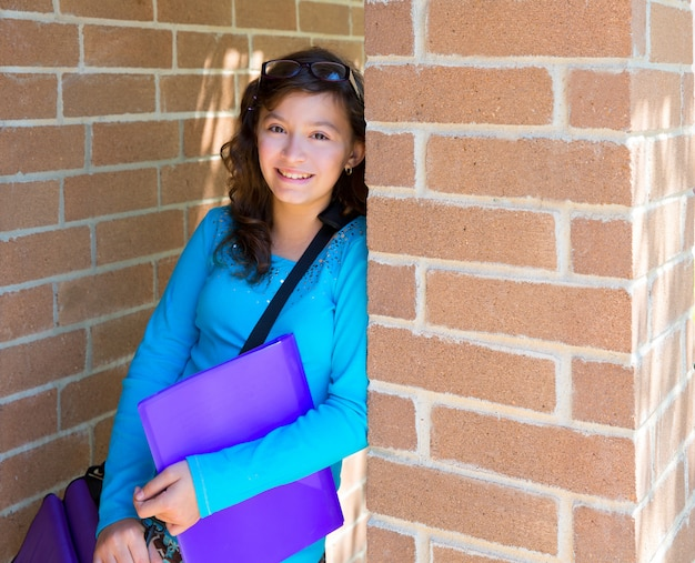 Adolescente della scolara al muro di mattoni della scuola felice