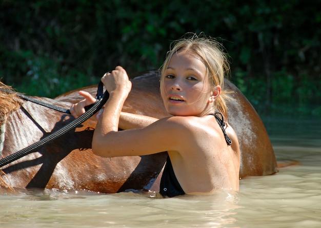 Adolescente e cavallo nel fiume