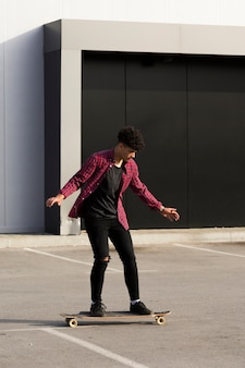 Adolescente etnico in camicia a quadri a cavallo longboard