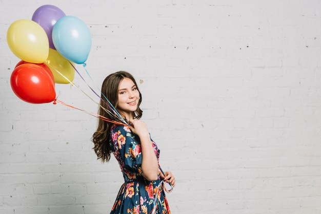 Adolescente felice che sta contro i palloni bianchi della tenuta del muro di mattoni
