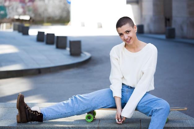 Adolescente femminile con i capelli corti che si siedono sul longboard alla via