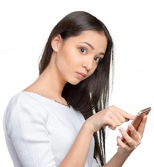 Adolescente femminile grazioso che per mezzo dello smartphone