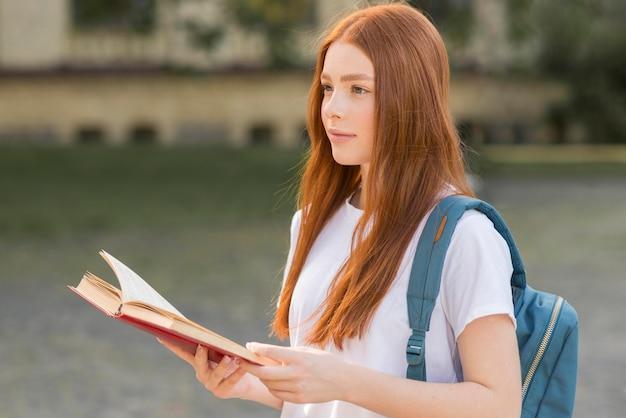 Adolescente grazioso che cammina attraverso il campus universitario