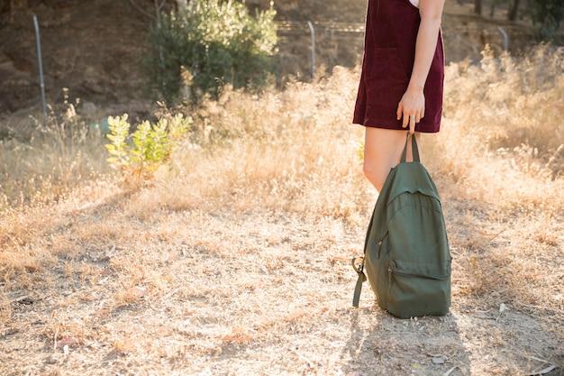 Adolescente in piedi con lo zaino in natura