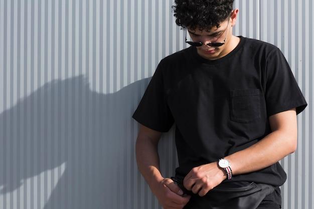 Adolescente maschio che sta contro la parete grigia