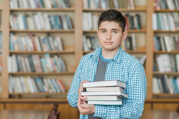 Adolescente maschio con una pila di libri