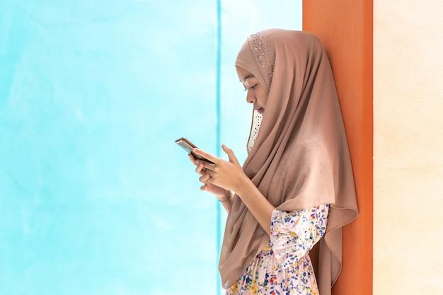 Adolescente musulmano asiatico che per mezzo del suo smartphone